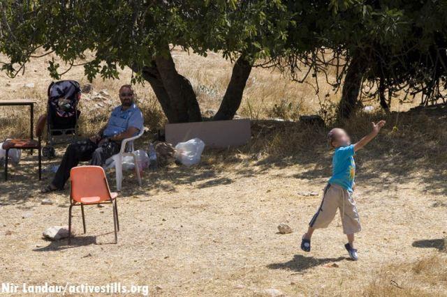 אב ובנו הצעיר מבלים זמן איכות ולומדים ליידות אבנים בנחת על פלסטינים, בשטח פלסטיני פרטי בחברון