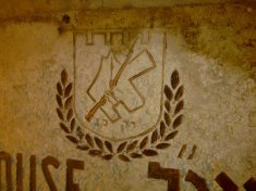 "The Irgun emblem: Both Banks Are Ours, ""The Only Way"" (רק כך), a rifle - and of course, olive branches..."